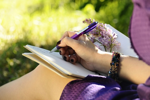 Notebook, pen and female hand close up, park