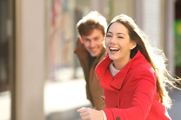 Happy couple running in the street