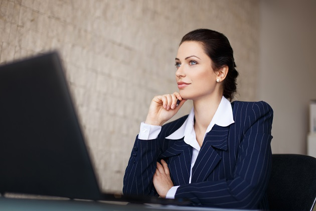 Confident businesswoman sitting at desk in office