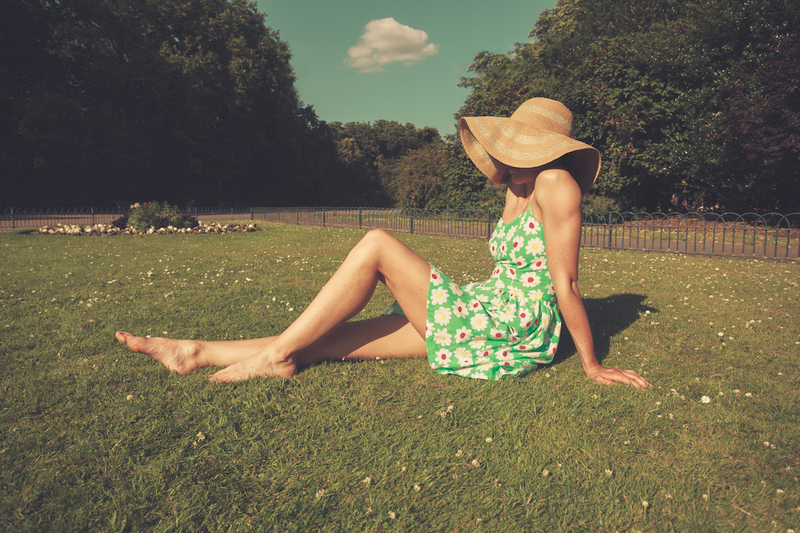 A young woman wearing a dress and a hat is sitting on the grass in a park