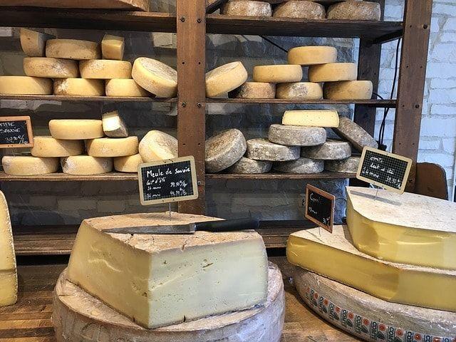 チーズ専門店の店内。奥のたなに平たい円柱状のチーズがたくさん積まれ、手前には量り売りのチーズが並んでいる。