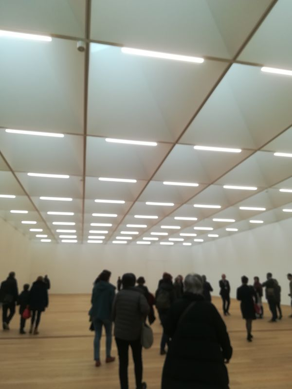 美術館の展示室の中を見学する人たち。天井は四角く区切られて天井窓の自然光とLEDで部屋は明るい