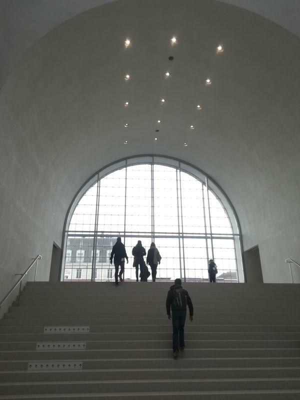 正面に階段がある。階段をのぼるとアーチ型の窓がみえる。光を背にして人々のシルエットがみえる。