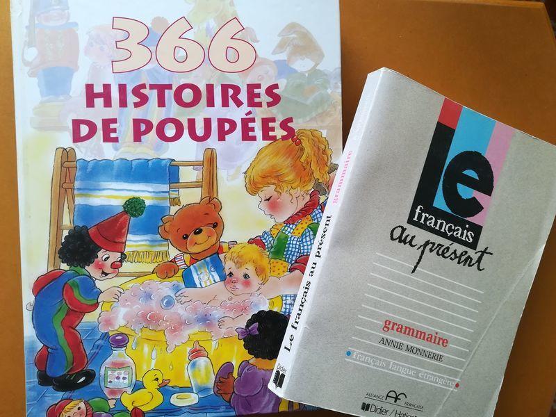 左側に表紙におもちゃの挿絵がついた小さな子ども向けのフランス語童話の本。右側にはフランス語文法の本。