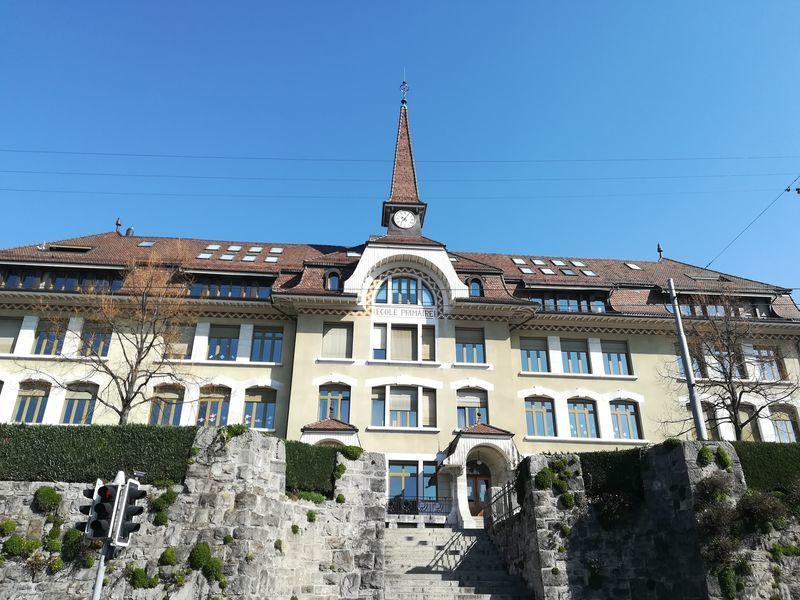 高い時計台のある小学校の建物。古い歴史を感じる建物。