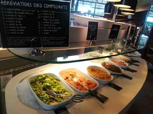 ビュッフェスタイルのレストラン。白い大きい皿に盛られたおかずが何種類も並んでいる。