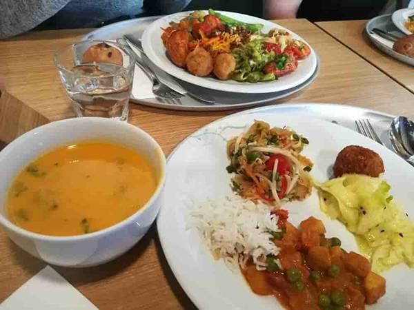テーブルに白い皿が何枚も置かれている。皿の上には数種類のおかずが盛られている。スープもある。