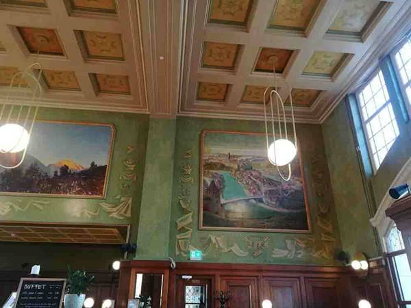 レストラン内装。壁にスイスの観光地の大きな絵が飾ってある。