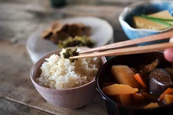 和食の食事がテーブルにある。手前のごはんに箸でおかずをのせている。奥にはおかずの乗った小皿がいくつか見える。