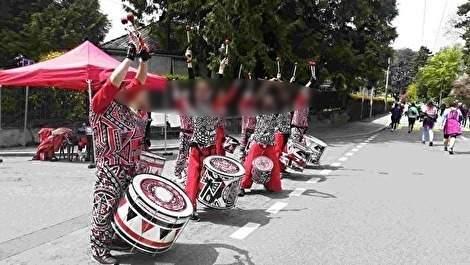 カラフルな衣装をきた音楽のバンドが沿道でランナーを応援している。