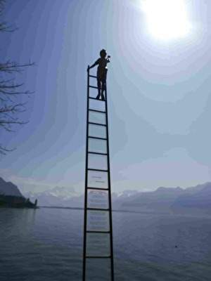 湖にたつはしごの上の子どもの銅像。子どもは太陽に手を伸ばしている。