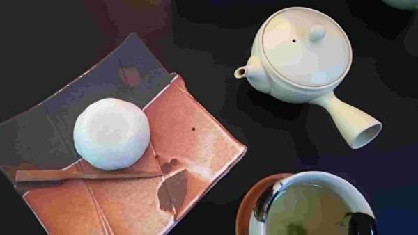 テーブルの上に白い急須、お茶の入った湯飲み、和菓子ののった皿がある。