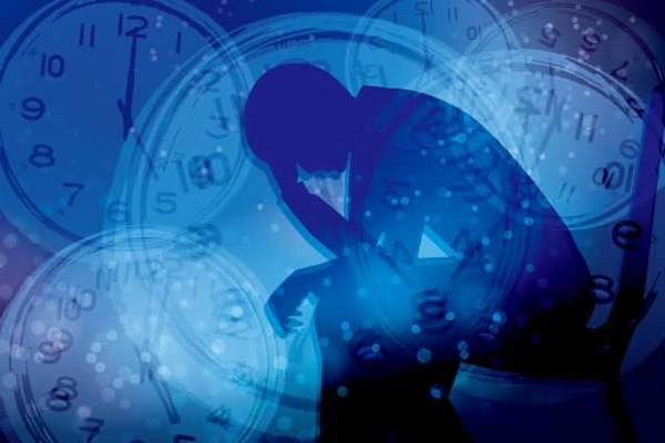 青い画面に映る影は男性で腰かけて頭を抱えている。奥に時計の針が重なっている。