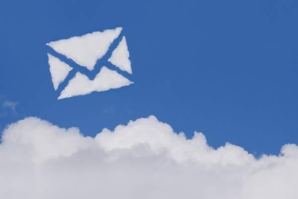 白い雲のある青空をバックに手紙の封筒の形の白い雲が浮かんでいる。