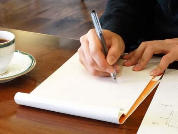 木のテーブルの上で便せんを広げて手紙を書いている手が見える。