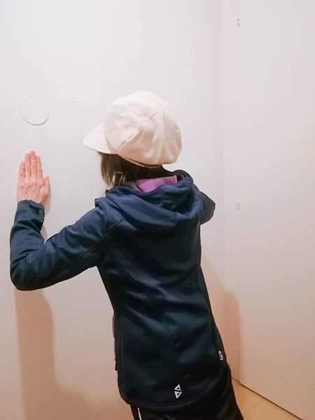 ベージュの帽子をかぶった女性が壁に向かって立ち腕をまげて腕立て伏せをしている