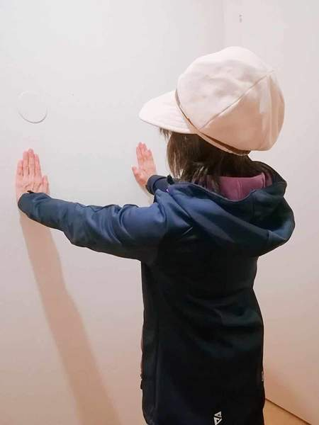 ベージュの帽子をかぶった女性が壁に向かって立ち両手を壁につけている