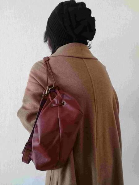 肩にショルダーバッグをかけた女性の後ろ姿。背中が丸くなっている。