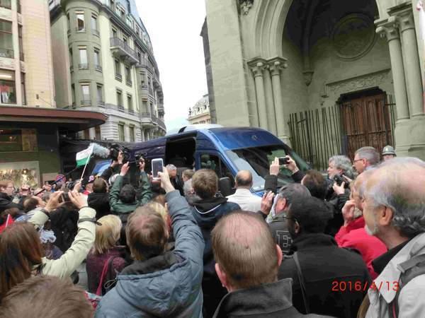 大勢の人がスマホのカメラで到着した青いバンから降りる政治家たちの写真をとっている。
