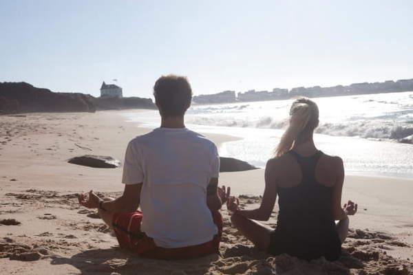 海岸の砂浜で座禅をする男女の後ろ姿