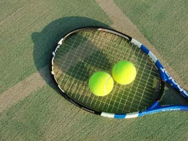 テニスコートに置かれたテニスラケットとテニスボールが2個
