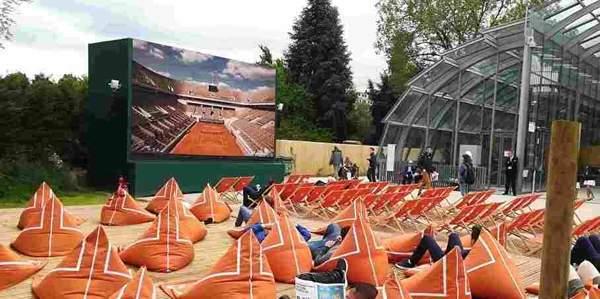 大きなスクリーンの前にオレンジのソファがたくさん地面に置いてあり、人々がくつろいでいる