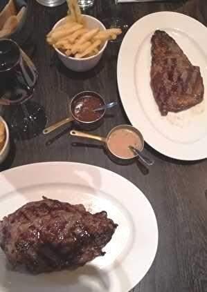テーブルの上に白い皿にのったステーキが2つ。フレンチフライの入った器もある。