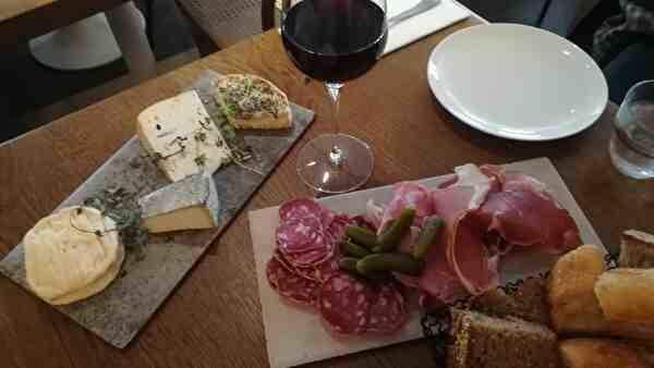 テーブルにチーズ4種類がのったプレートとハム類のプレートがある。