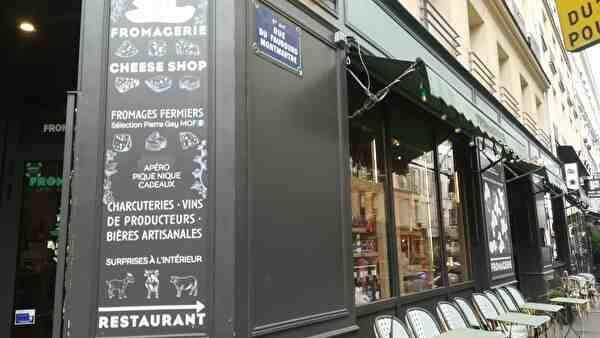 チーズ専門レストランの表の写真。外壁にそってテーブルとイスが並んでいる。