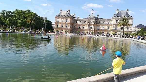 美しい宮殿の前に人工の池がひろがり子どもがおもちゃのヨットを浮かべて遊んでいる。