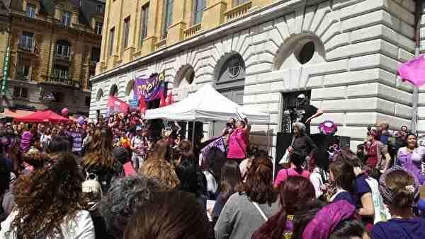 紫やピンクのTシャツを着た女性たちがストライキのため大勢広場に集まっている。