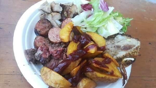 バーベキューの肉の盛り合わせ。じゃがいものフライやサラダも添えられている。