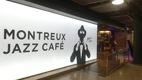 白地に黒い文字でモントルージャズカフェという文字とシンボルの帽子に蝶ネクタイのミュージシャンの絵が描いてある。