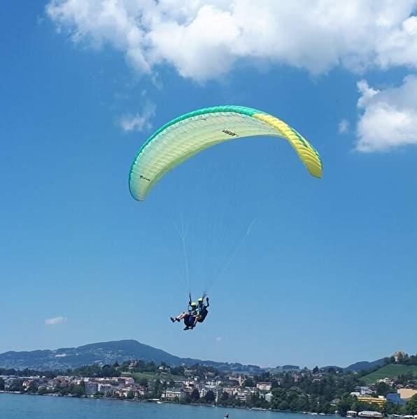 青い空を背景に緑の2人乗りパラグライダーが湖に舞い降りてくる様子。