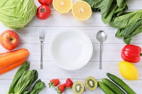 白いテーブルの真ん中に白い皿とスプーンとフォークが並べられている。まわりを取り囲むようにしてレタスやトマトなど野菜が並んでいる。
