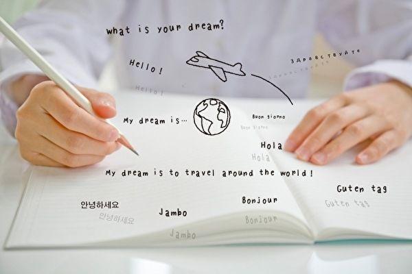 白いノートを広げて語学学習している。ノートの上には、小さな文字で世界の言語でこんにちは、という言葉が浮かんでいる。