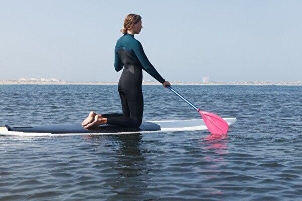 スタンドアップパドルのボードの上にウェットスーツを着た女性が膝立ちしてパドルを漕いで進んでいる。