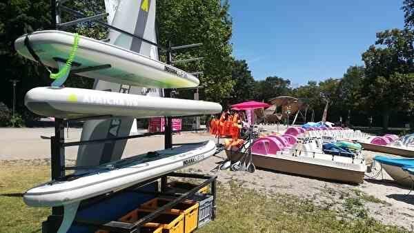 砂浜の棚に、サーフィンボードが並べてある。奥には、足漕ぎボートがたくさん水際に並べられている。