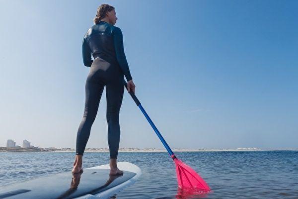 ウェットスーツの女性がスタンドアップパドルに立ち、パドルを漕いで水面を進んでいる。