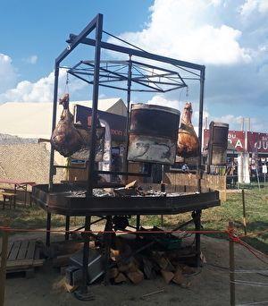巨大な肉が大きなバーベキューの機械で焼かれている。