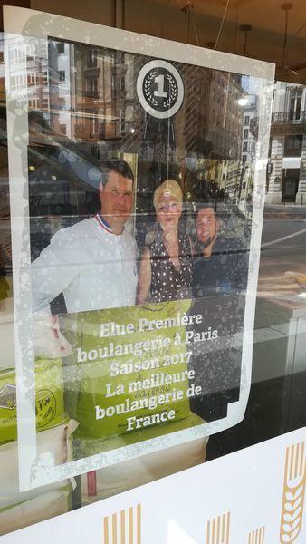 窓に貼られたポスター。左が白いシェフの上着を着た男性。真ん中に女性。右にひげをはやした若い男性。