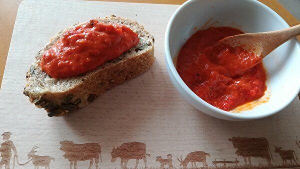 木のトレイの左側にソースをのせたパンが一切れ、右側には白い器に入ったソースに木のスプーンが添えてある。
