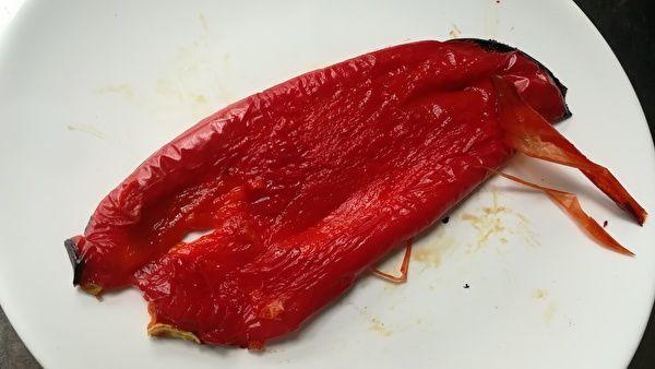 白い皿の上に皮をのぞいた赤パプリカが置いてある。