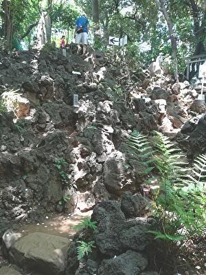 溶岩をかためた山道の上に登山客が見える。