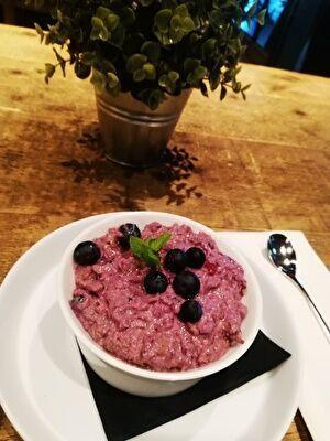 テーブルの上に白い器にきれいな紫色のミューズリーが盛られている。ブルーベリーものせてある。