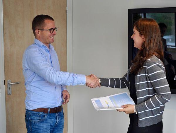 男性と女性がオフィスで握手をしている。