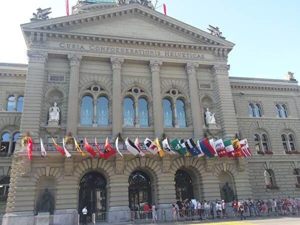 スイス連邦議会議事堂正面。国旗のほか、各州の旗が飾られている。見学者が列を作っている。