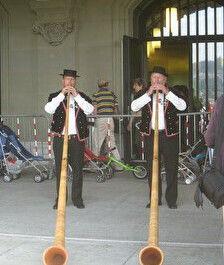 スイスホルンを演奏する民族衣装の男性2人。