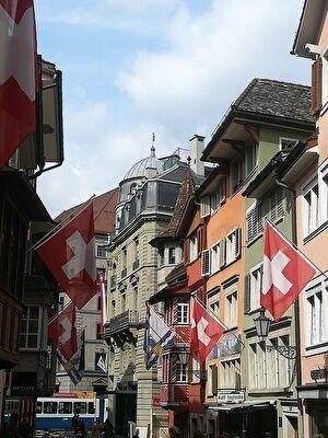 ヨーロッパの古い建物が並ぶ街並み。建物それぞれにはスイスの旗が飾られている。