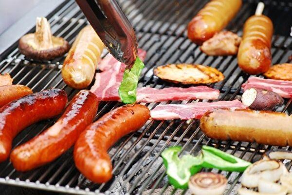 バーベキューのコンロの鉄板の上にソーセージ、肉、野菜など食材が美味しそうに焼けている。